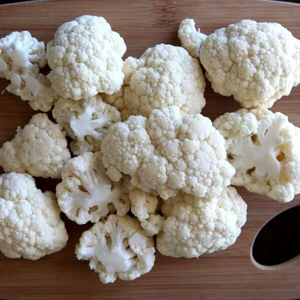 Fresh cut cauliflower laying on a cutting board for a visual.