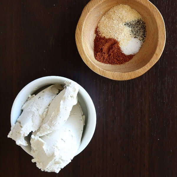 One small wooden bowl with spices and another with dairy free cream cheese.
