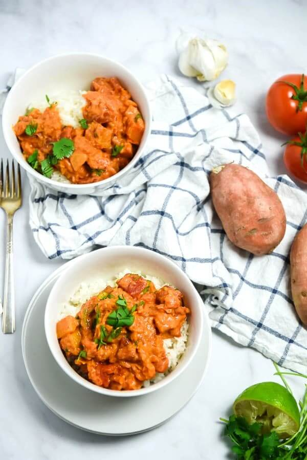 Overhead view of two bowls of sweet potato curry set against white and fresh ingredients on the side.