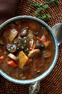 Close overhead photo of a bowlful of vegetable stew with a spoon on the side.