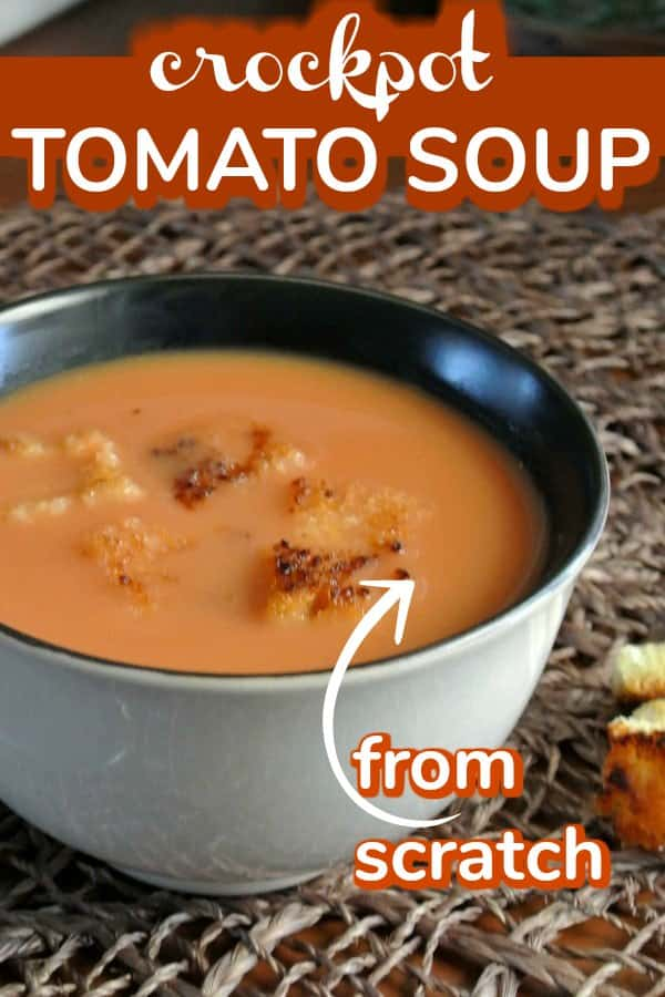 Cropped beige bowl of vegan tomato soup with croutons as garnish and text for pinning.