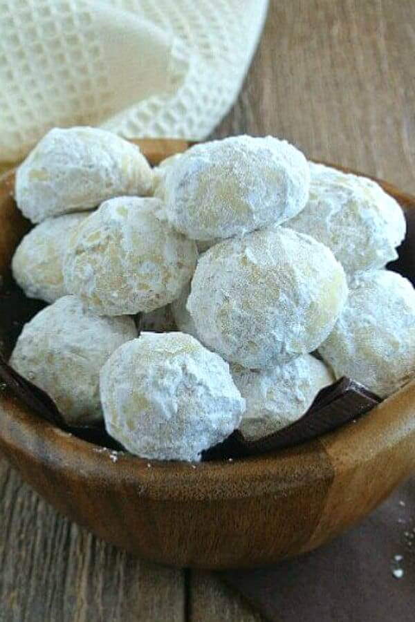 Wooden bowl full of cookie balls covered with powdered sugar for one of the 27 vegan Mexican style recipes in this roundup.