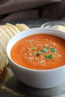 Cropped white bowl of dairy-free tomato soup with vegan parmesan cheese sprinkled on top.