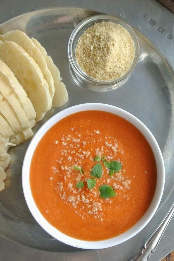 Ovehead photo of tomato soup sitting on a pewter plate with vegan Parmesan cheese.