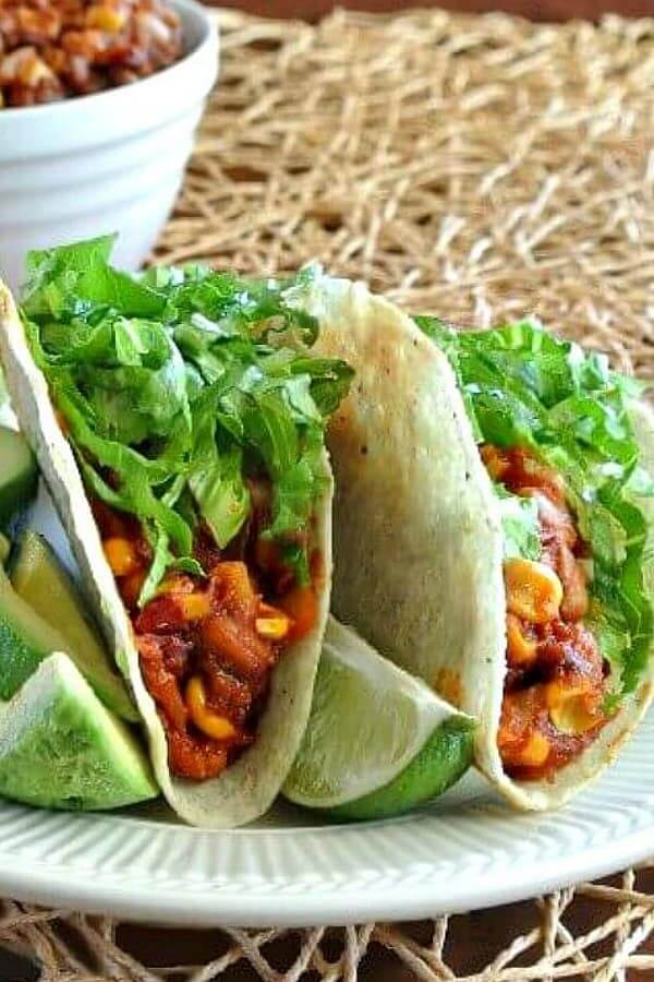 Two taco shells filled with a hot pinto beans and corn mixture with greens and avocado.