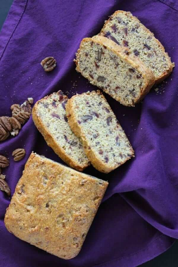 Overhead photo of slices off of a loaf of sweet cornbread on a purple cloth napkin.