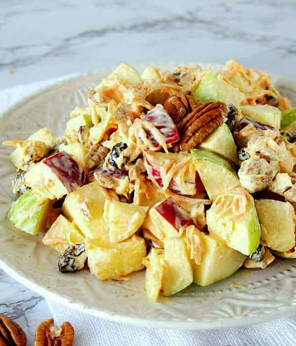 Angled plate full of tossed apple salad on a white napkin and pecans sprinkled around.