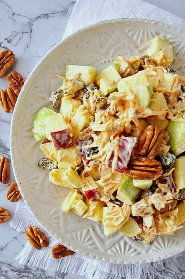 Overhead photo of a cropped white plate full of tossed apple pecan salad.
