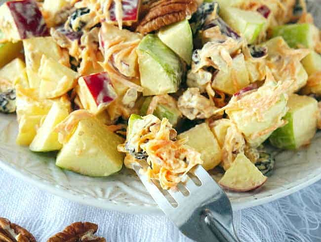 Wide view of a forkful of apple salad leaning against the salad plate.