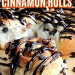 Close up of one chocolate covered cinnamon roll in front of a batch of nine.
