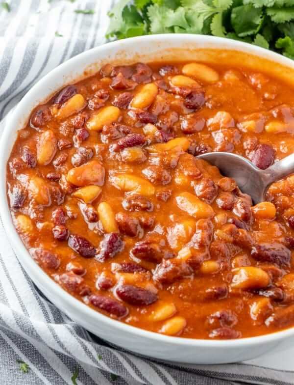 A spoon is sliding through a big bowl of baked beans just in time for dinner.