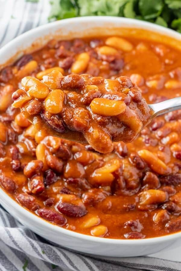 A spoonful of baked beans is being held close to the camera lens to show the rich textures.