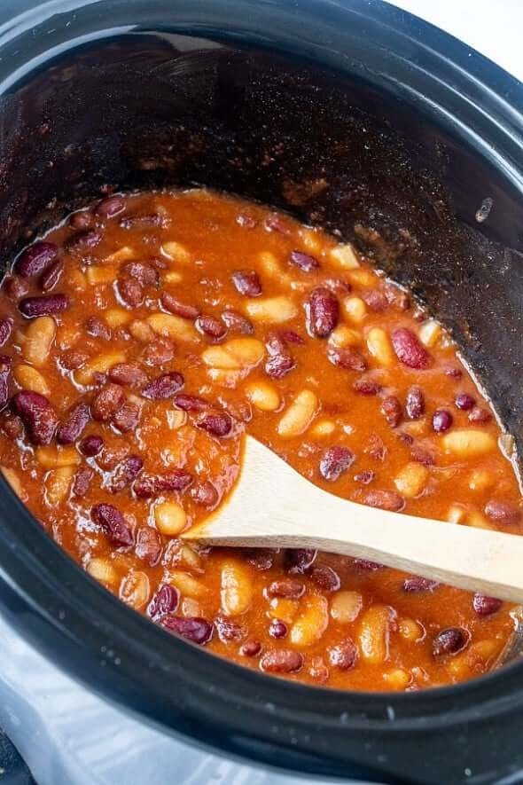 A wooden spoon is stirring the Vegetarian baked beans in the slow cooker.