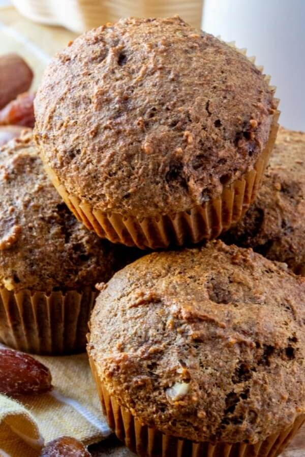 A muffin almost filling out the whole photo and sitting on others.