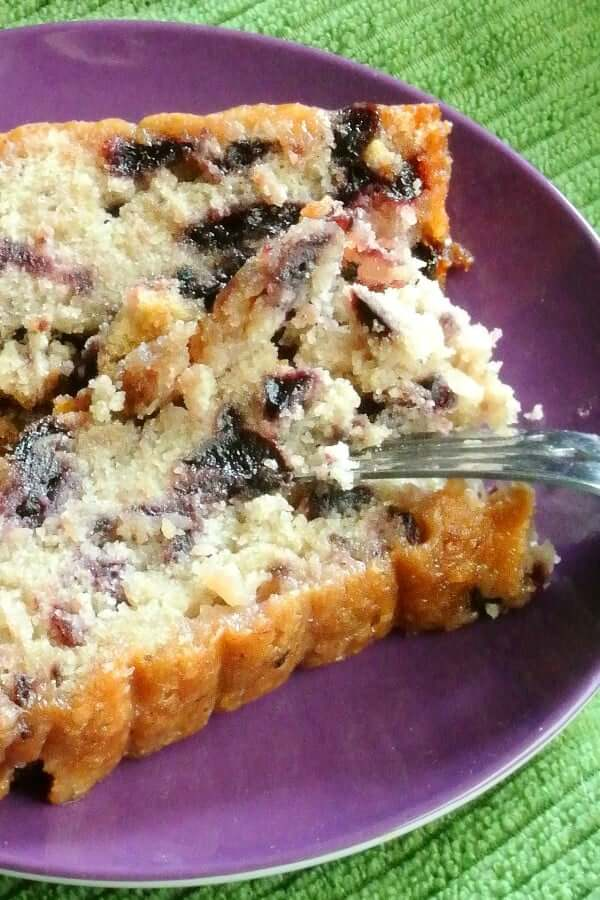 A bite of moist blueberry cake is flipped over to show how tender the bite is.