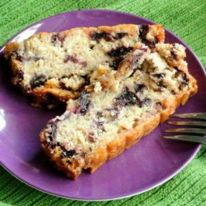 Two slices of a moist cake showing blueberries through the slices.