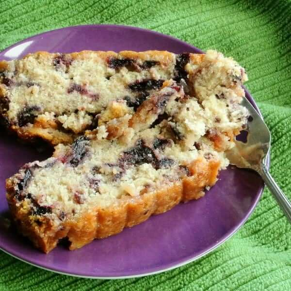 Two close up slices of a moist cake showing blueberries and tender cake on a fork.