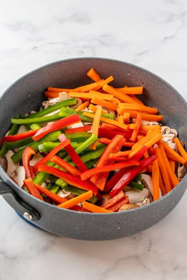 A skillet full of fresh red, green and ivory veggies.