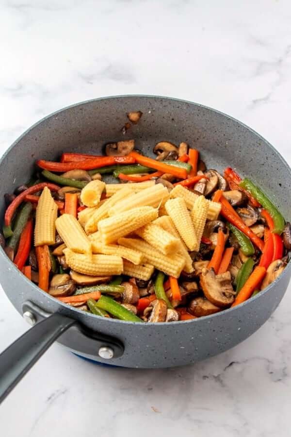 A skillet full of sauteed red, green and ivory veggies and baby corn on top.