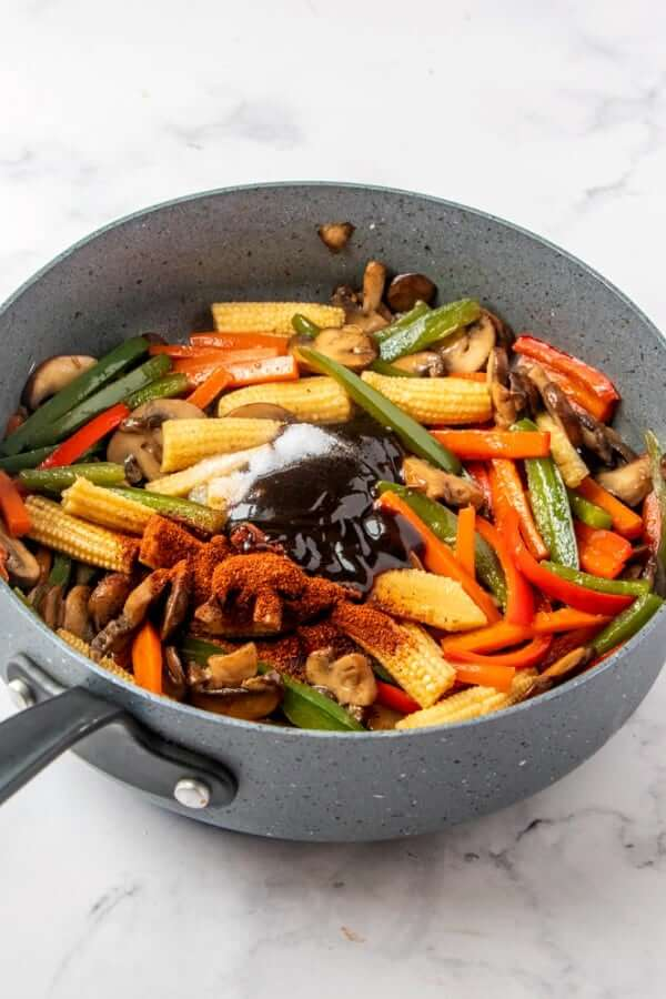 A skillet full of sauteed red, green and ivory veggies with spices and sauce on top waiting to be cooked into the meal.