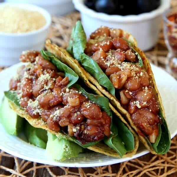 Square photo of two close up pinto beans tacos on a white plate and open straw mat.