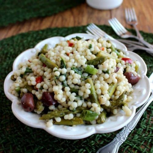 Centered scalloped bowl filled with Israeli couscous salad and dotted with asparagus and purple olives.