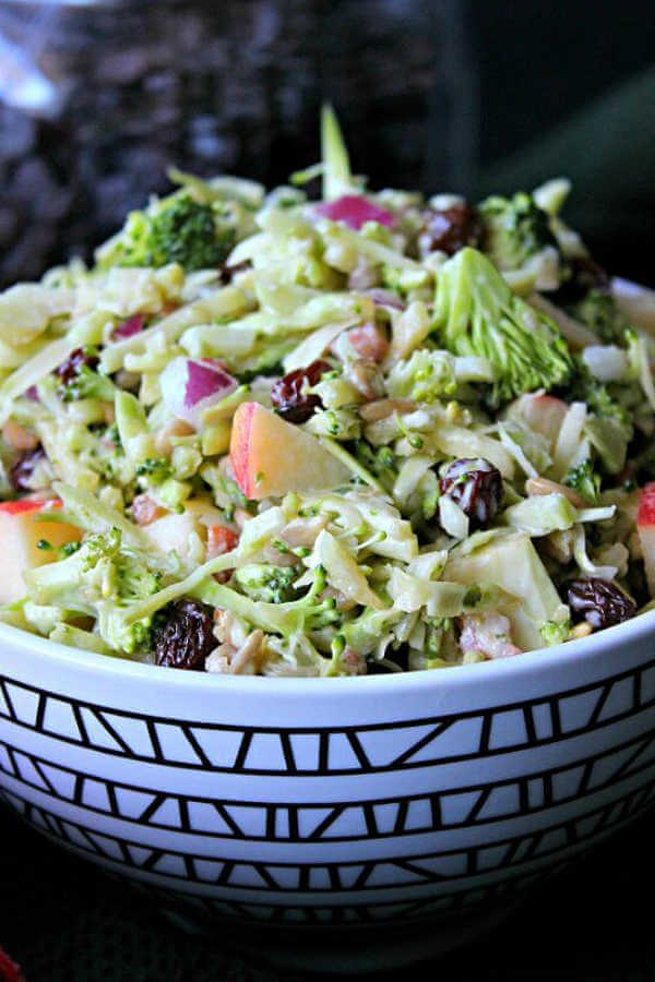 Super close cropped photo of a geometric patterned bowl filled to overflowing with green and red vegetable salad.