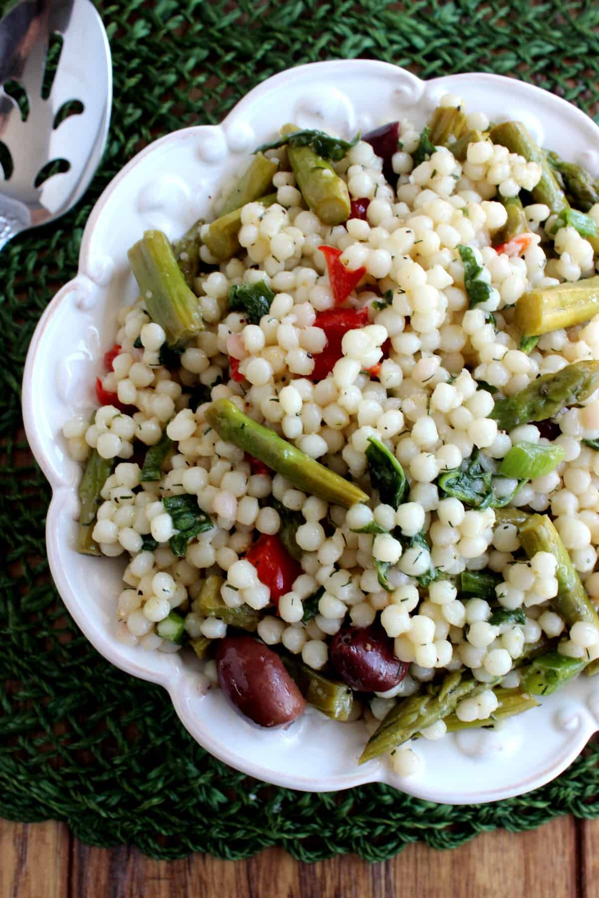 Overhead view of a cold salad in a white bowl filled with couscous, asparagus and more veggies.