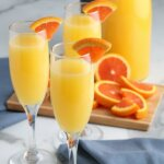 Styled photo with three champagne glass flutes filled with mimosas and quarter slices of an orange.
