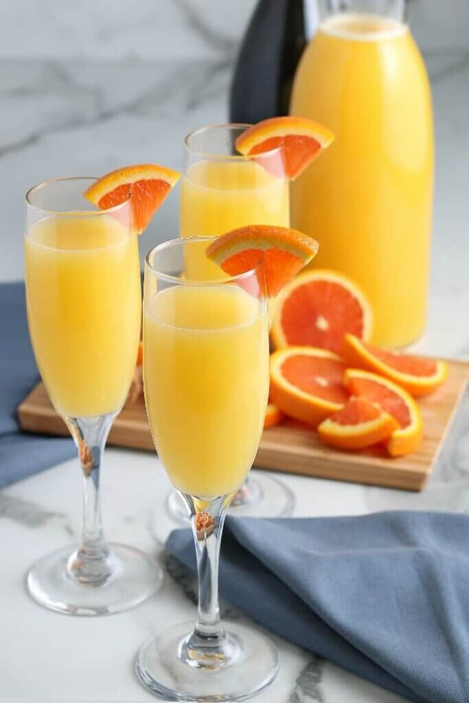Styles photos with three champagne glass filled with mimosas and quarter slices of an orange.