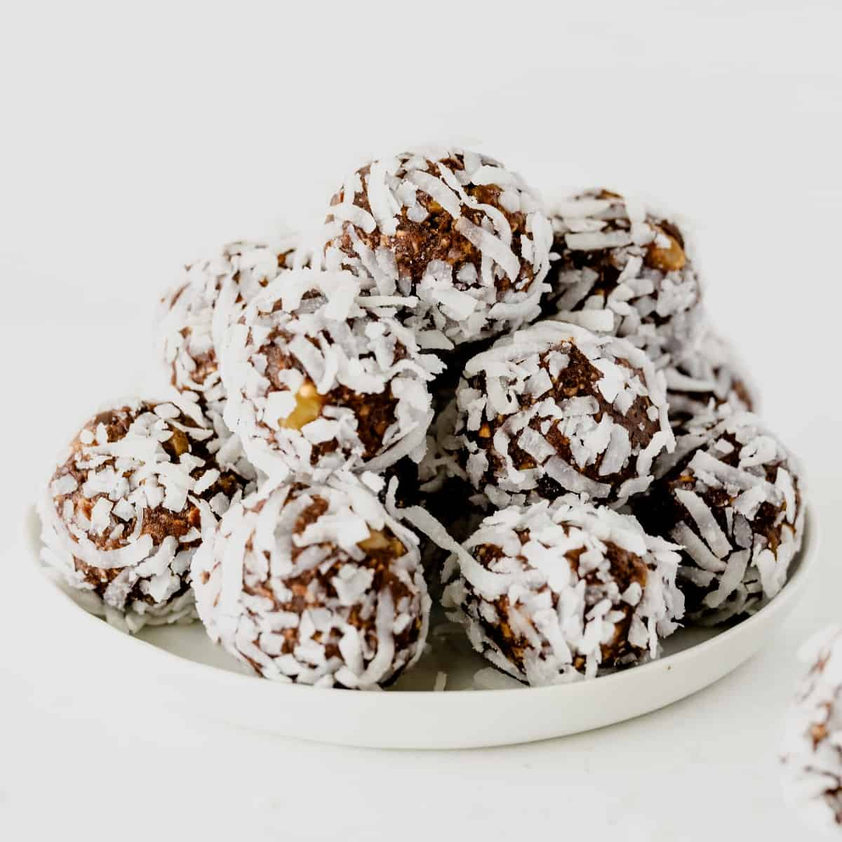 A perfectly centered white plate full of coconut covered chocolate balls