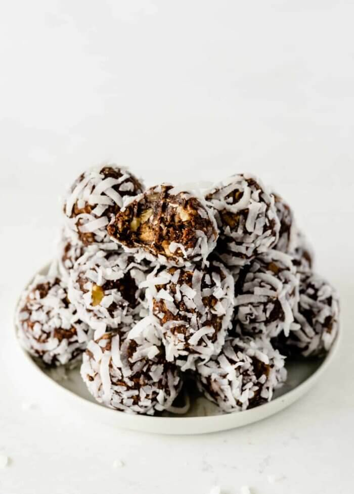 A white plate is piled high with chocolate date energy balls with the top one having a bite out of it.