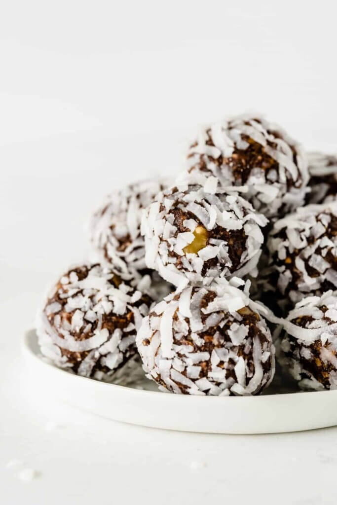A close-up of chocolate date balls covered in coconut and stacked on a white plate against all white.