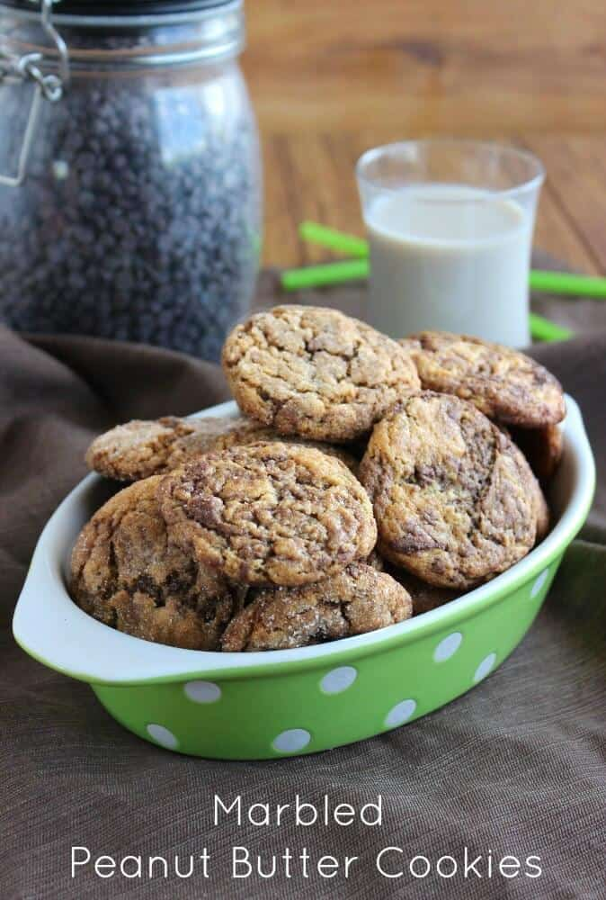 A bowlful of cookies is sitting in front of a jar of chocolate chips and a glass of dairy free milk.