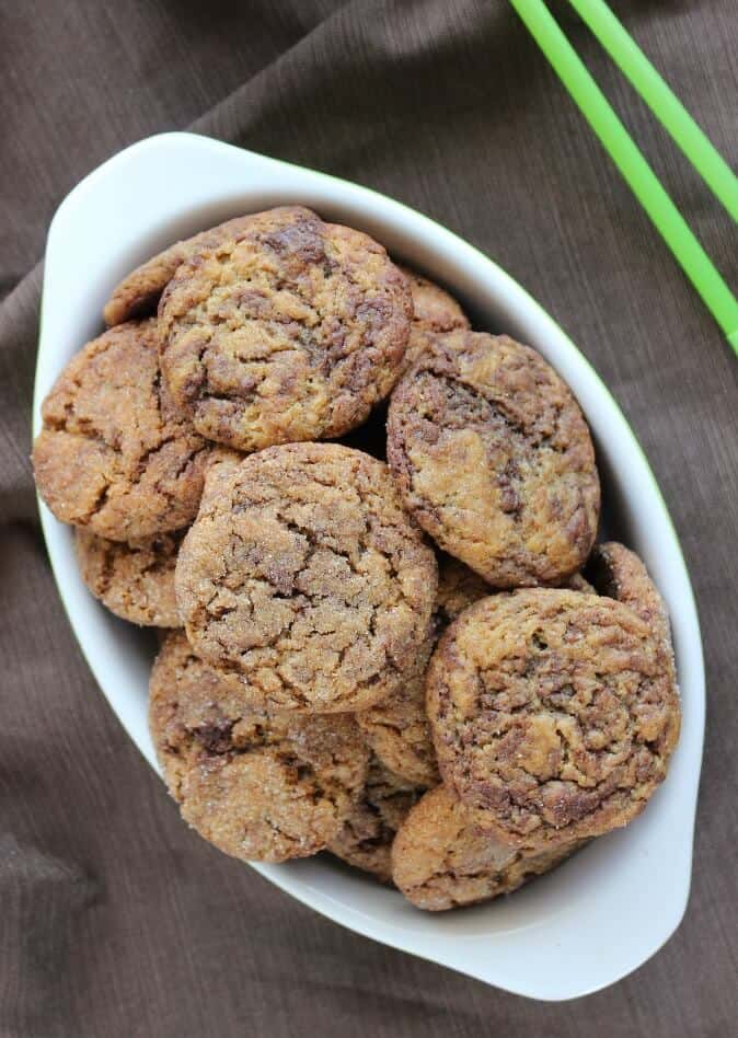 Overhead photo of a bowlful of cookies against a chocolate brown cloth.