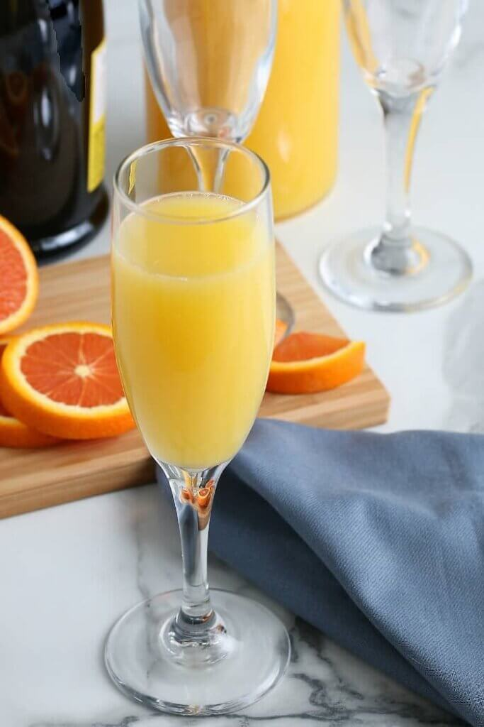 One champagne glass is filled with the best mimosa and is waiting for a garnish.