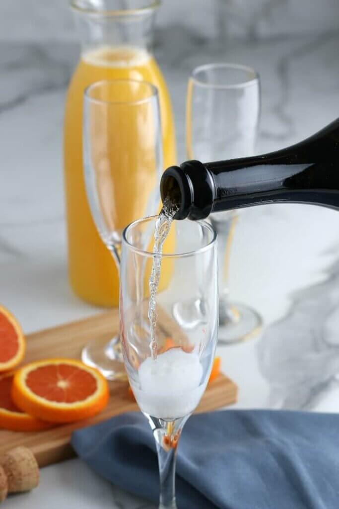 Sparking wine is being slowly poured into an empty champagne glass with slices of oranges behind on a cutting board.