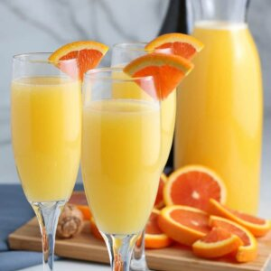 Three filled and garnished champagne filled with golden mimosas with lots of orange slices for garnish behind.