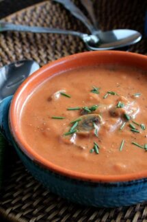 Cropped blue handled bowl filled with thick creamy tomato soup on a straw mat.