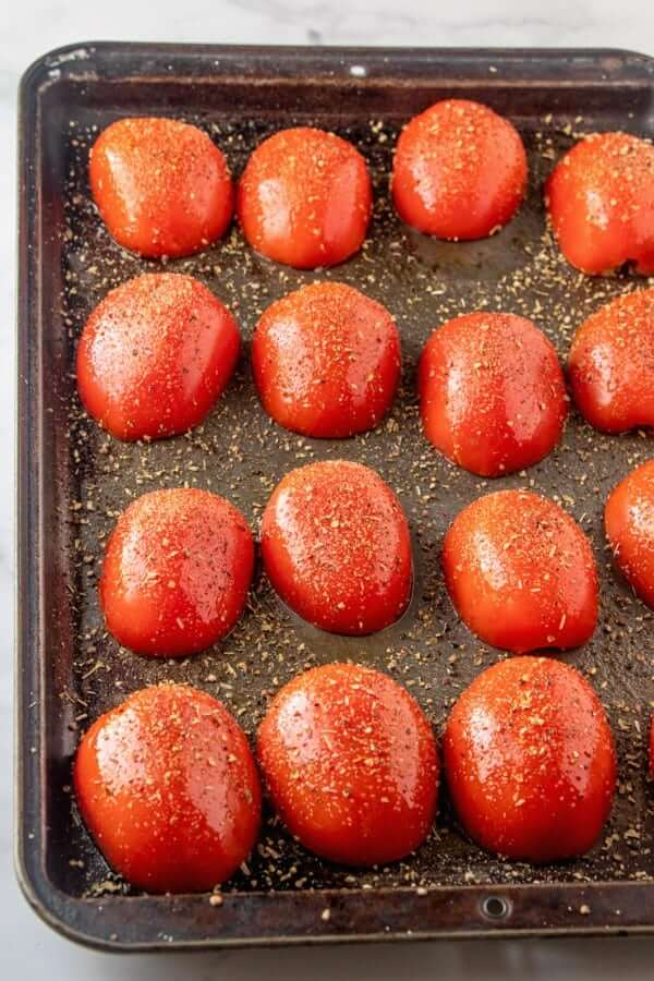 Overhead view of roasted plum tomatoes on a baking sheet.