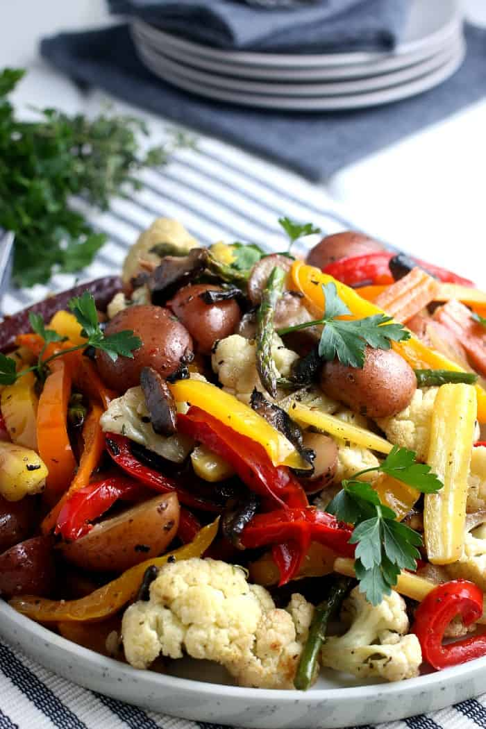 Large serving platter stacked with a mix of colorful roasted vegetables.