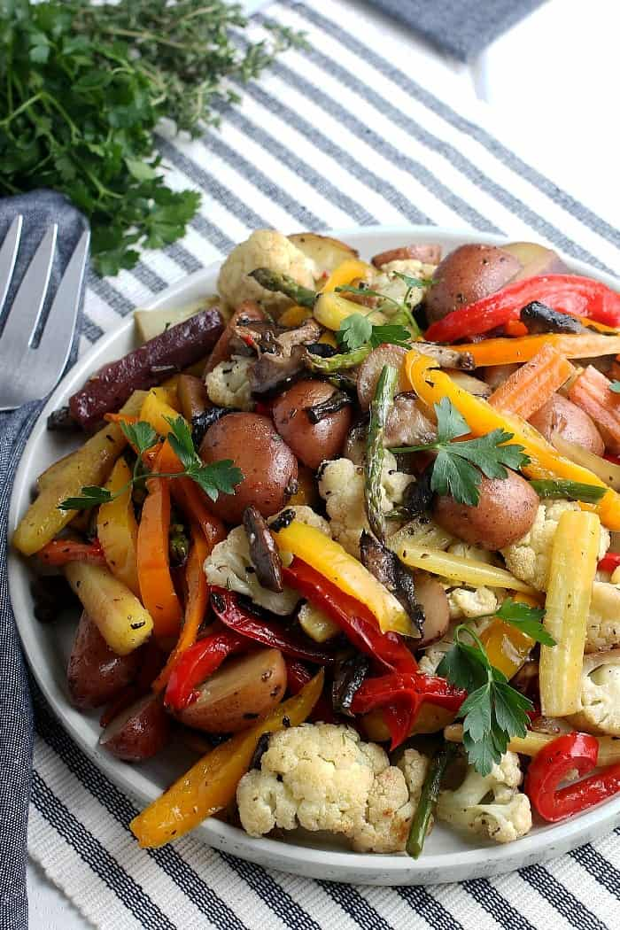 Angled plate filled with sheet pan oven roasted roasted vegetables in about colors with a serving fork alongside.