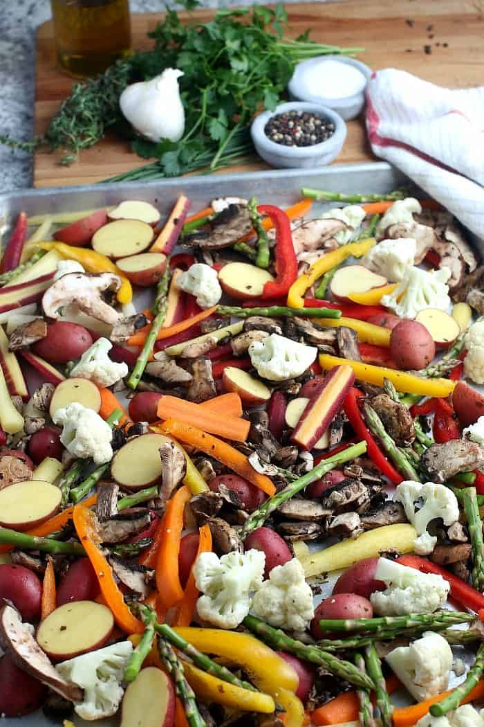 Raw but pared and prepared fresh vegetables resting on a sheet pan.