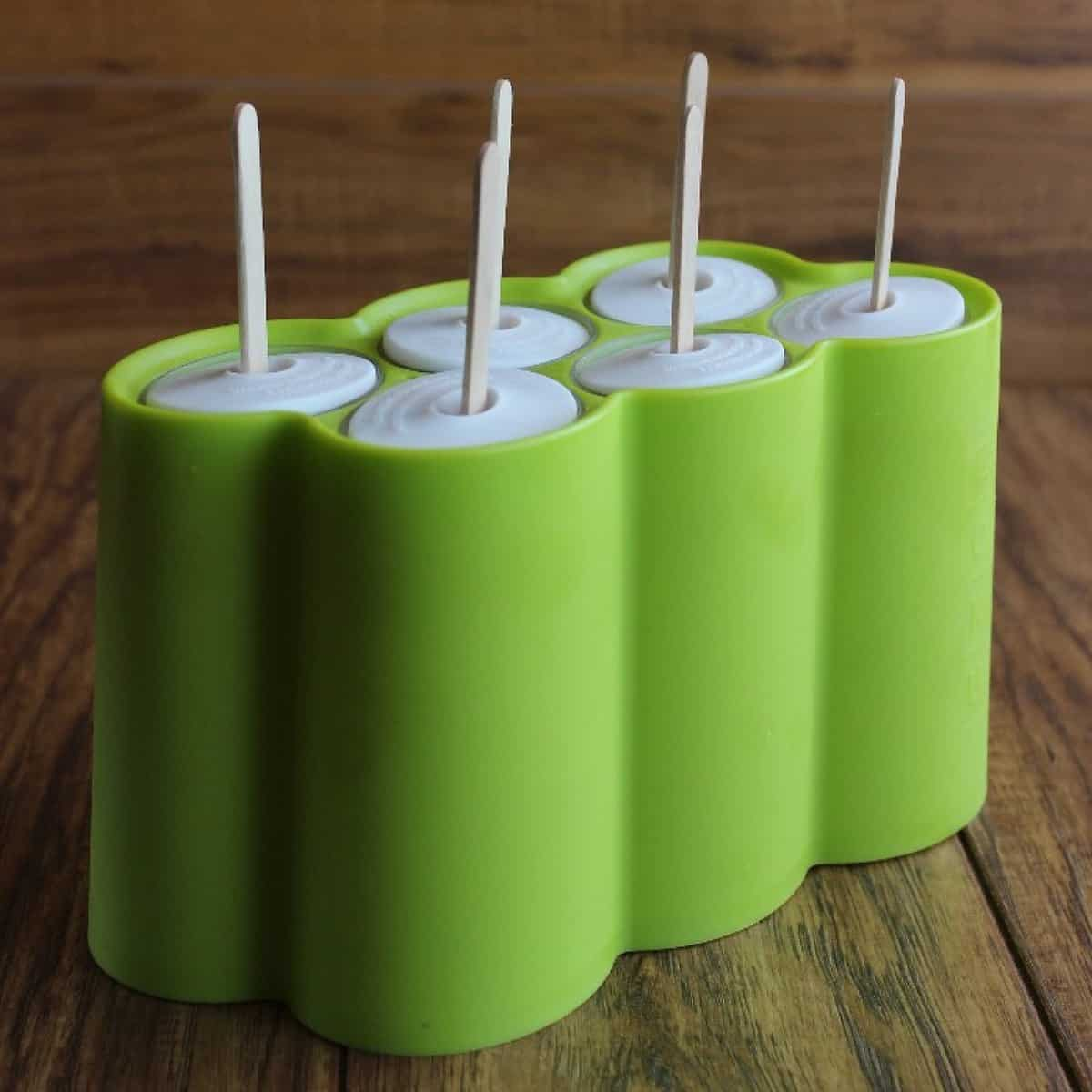Side view of the popsicle mold in a lime green color with the wooden pop sticks coming out the top.