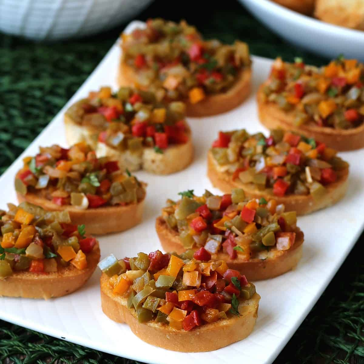 Vegan Christmas recipes appetizer of crostini toasts with balsamic bell pepper bruschetta in rows.
