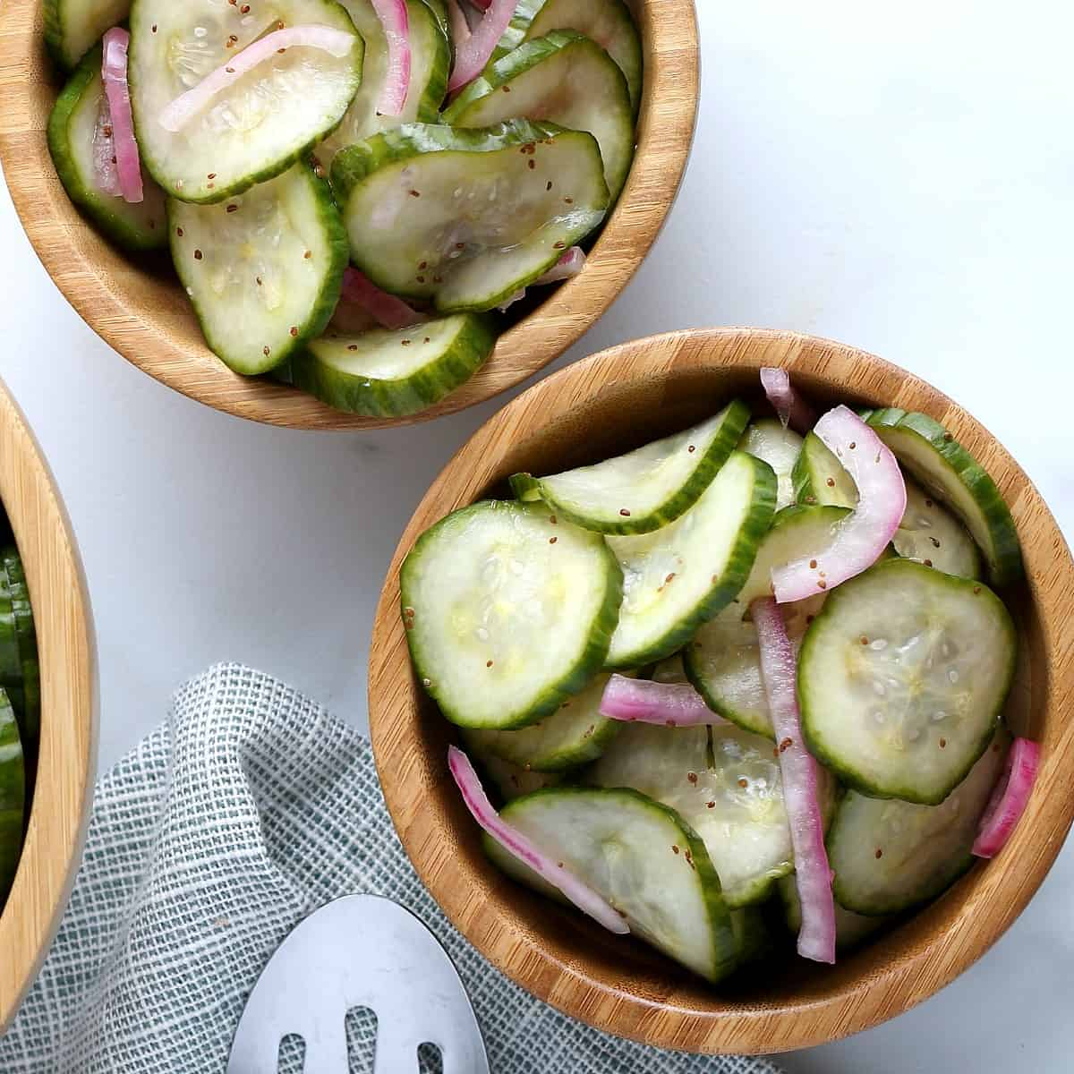 Overhead view of two wooden bowls filled with colorful green, white and deep purple veggie colors for this cucumber vinegar salad recipe.