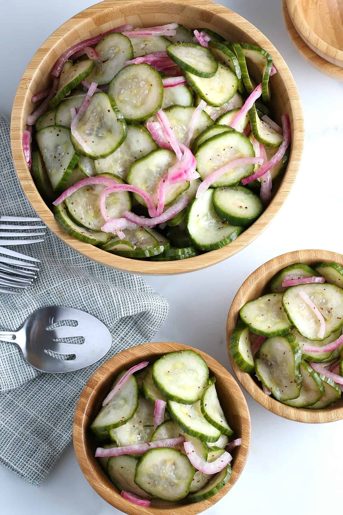 Overhead view of the large serving bowl and two smaller individual bowls full of cucumber vinegar salad with forks and a slotted spoon on the left.