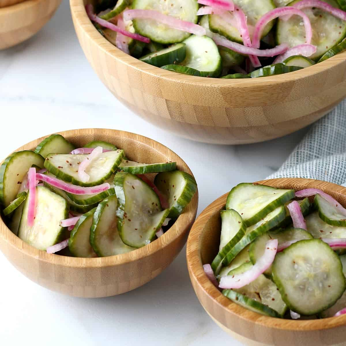 Two small single serve wooden bowls are filled with cucumber vinegar salad with the large bowl sitting behind.