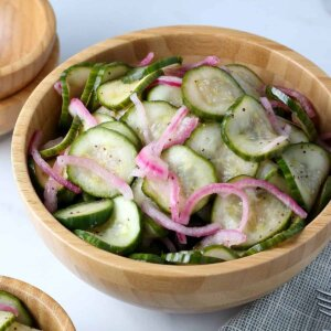 A large wooden bowl is tilted forward and filled with green cucumber slices and thinly sliced red onions.