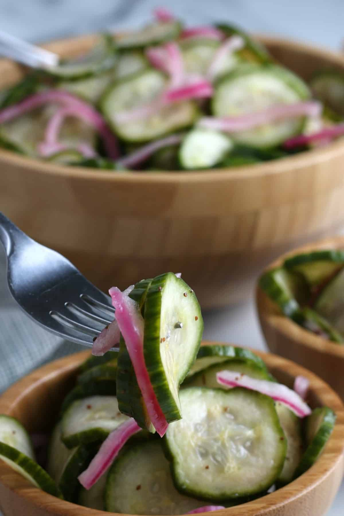 Closeup photo of cuke and onion slices on a fork and coming right for your mouth.